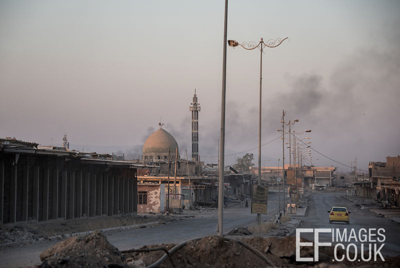 Taxi Drivers are back at work in liberated areas of West Mosul as airstrike smoke rises into the evening air on the other side of the frontline. Mosul, Iraq, 4th June 2017
