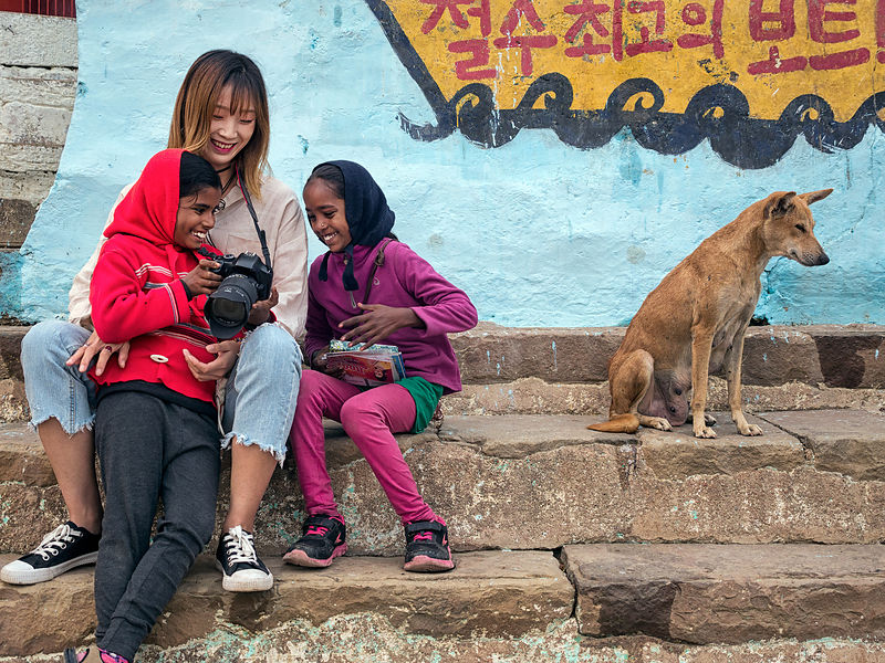 This photograph of young girls enjoying a glimpse at a tourist's camera was shot at the Ghats of Varanasi.