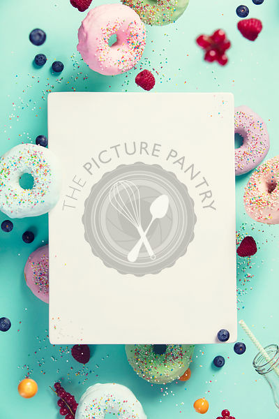 Sweet and colourful doughnuts with sprinkles and berries falling or flying in motion against blue pastel background