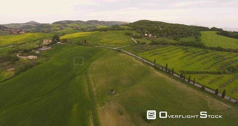 Aerial, beautiful landscape with a pond in the middle of hills and fields on sunset in Val d Orcia in Tuscany, Italy