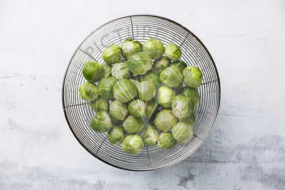 raw Brussels sprouts in colander on white background