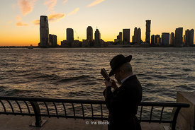 Hasidic Jews praying at the Hudson river in Lower Manhattan in New York City with the New Jersey skyline in the background.