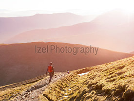A hiker and their dog walking down the mountain ridge of Scar Crags and Causey Pike with the early morning sun in the English Lake District, UK.