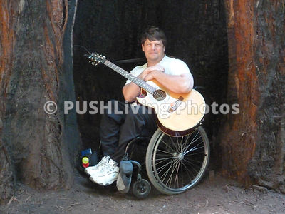 Man in a wheelchair playing a guitar in a giant redwood