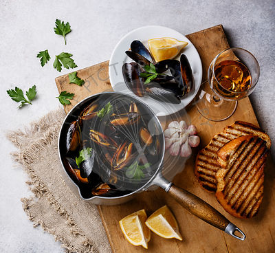 Mussels in cooking pan with parsley and wine on white background