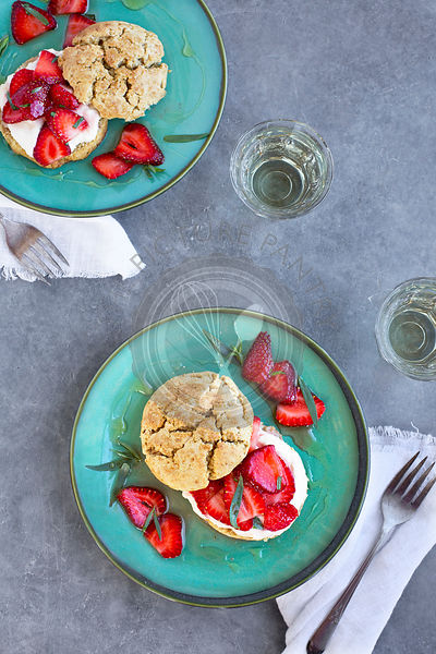 Strawberry Ricotta Shortcakes with honey and tarragon. Photographed from top view on a blue/grey background.