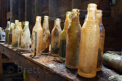 Soda bottles sit dusty and cob-webbed, untouched for 30 years in the defunct cannery of the Butedale ghost town, Great Bear Rainforest, British Columbia