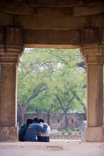 India - New Delhi - Boys huddle and talk among the ruins of Hauz Khas Village