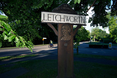 UK - Letchworth Garden City - A cyclist rides past a road sign bearing the image of the founder of Letchworth Garden City, Ebenezer Howard