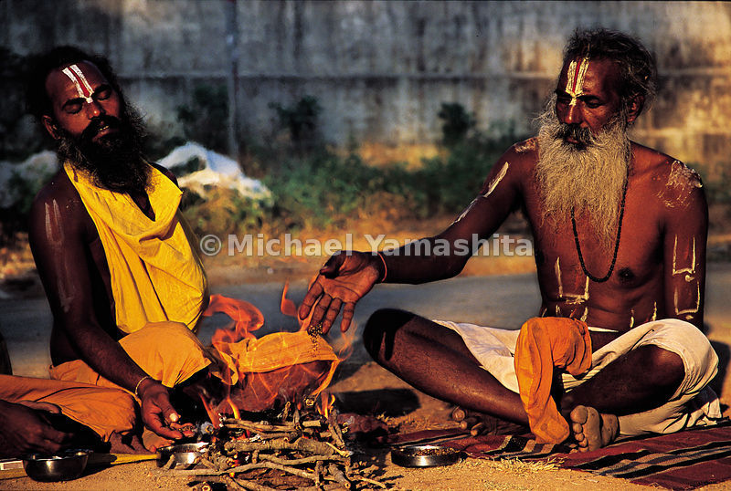 Two men sit around a sacred fire they build together.