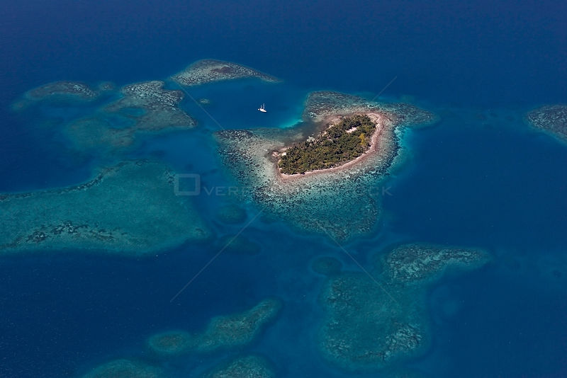 Aerial view of coral caye (a small island), with sailboat, inside southern Belize barrier reef, near Placencia. Belize Barrier Reef Reserve System, a UNESCO Natural World Heritage Site. Belize, Central America. Caribbean Sea.