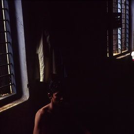 Two students, one admiring himself in a mirror, relax in their room at the Kerala Kalamandalam