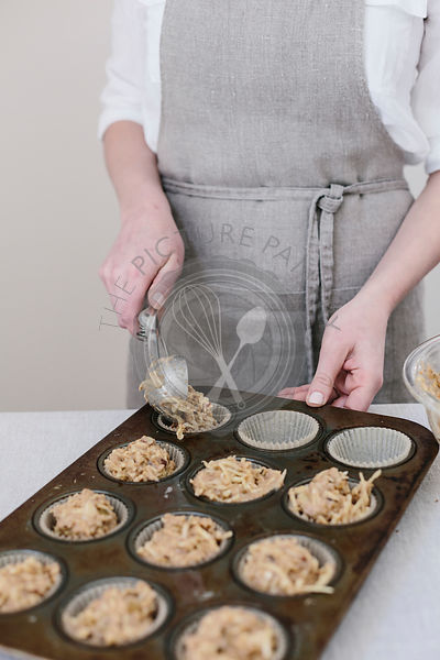 A woman is photographed from the front view as she distirbutes muffin batter into the muffin tin.