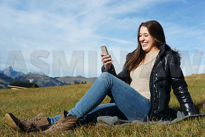 Pretty Girl with mobile phone in the mountains