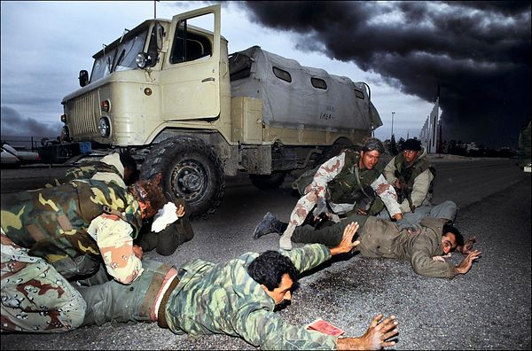 Iraqi soldiers arrest by US special forces . In the sky, black smoke from burning oil wells