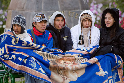 A group of college students huddle under a blanket while waiting to practice a dance routine for Cusco Week in Cusco, Peru (mornings in Cusco are cold)