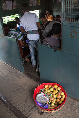 A man sells apples on the Calcutta local train, Patipukur, Kolkata, India