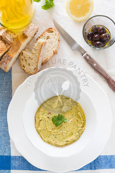 Coriander and lemon hummus, with rustic bread, olives, olive oil and lemon served on blue and white linen tablecloth