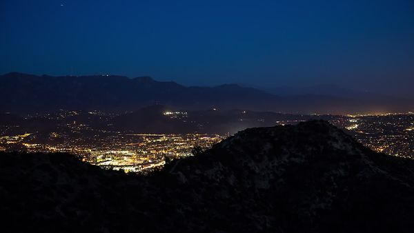 Bird's Eye: Silhouette's Of Mountains Over Civilization At Night