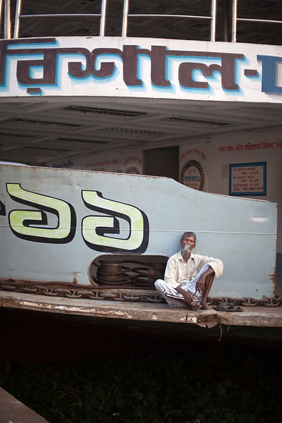 Bangladesh - Dhaka - An old man sits smoking on a ferry at the Sadarghat ferry terminal
