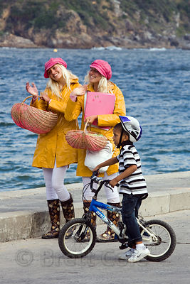 A boy riding his bicycle talks to Norwegian Twins who are raising money for college by entertaining tourists with song and dance, Cape Town, South Africa