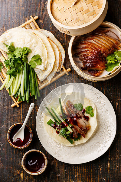 Peking Duck serving size with fresh cucumber, green onion, cilantro and roasted wheaten chinese pancakes with sauce Hoysin on wooden background