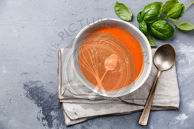 Tomato soup Gazpacho in bowl and green basil on grey concrete background