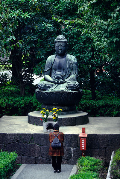 A woman prays in front of a statue of the Buddha