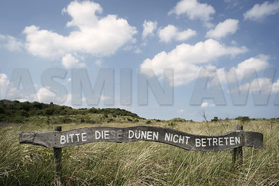 Old warning sign on the North Sea coast reminding people not to step on the dunes and grass in a nature reserve..Germany