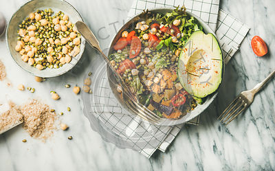 Flat-lay of vegan dinner bowl with avocado, grains, beans, vegetables