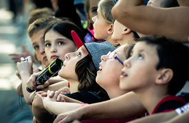 Schoolkids watching a helicopter hovering above the race at Grand Prix Cycliste de Québec; September 11, 2015