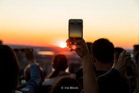 A woman takes a picture of the sunset from the top of the Rockefeller Center in New York City.