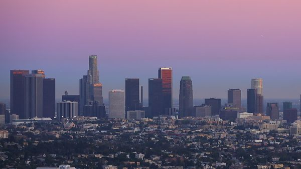 Medium Shot: Sun Sets Quickly Over A Spread Of Neighborhoods In Front Of L.A. Skyline