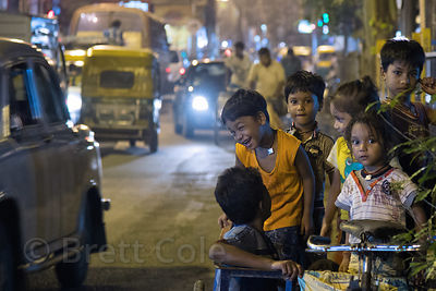 Children play in a cart on the side of a busy road at night, Rabindra Ganan, Kolkata, India