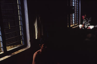 India - Kerala - Two students, one admiring himself in a mirror, relax in their room at the Kerala Kalamandalam