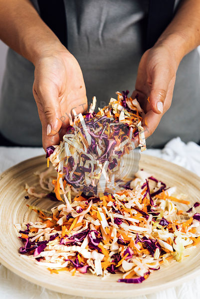 A woman tossing shredded carrot, white and purple cabbage in a wooden bowl photographed from front view.