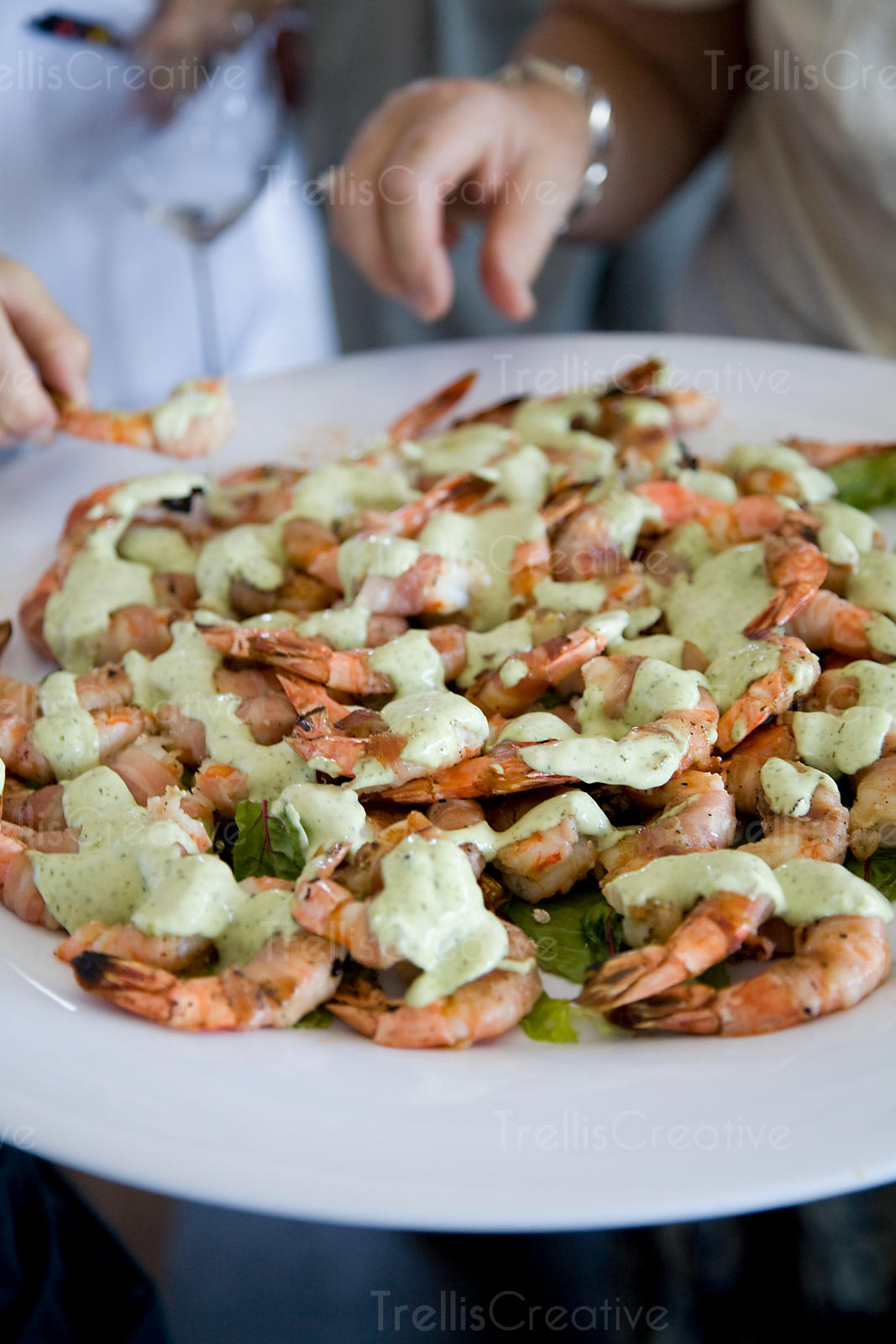 Guests enjoy eating seasoned shrimp from a platter