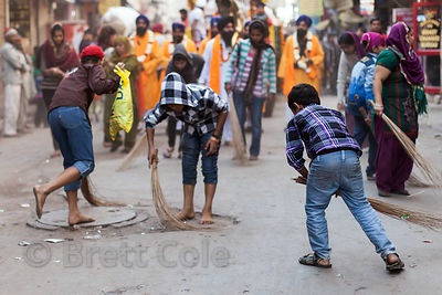 Boys sweep up after a Sikh parade in the Paharganj area of Delhi, India