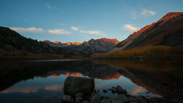 Medium Shot: Sunrise With Light Clouds & Peaks Over A Placid Mountain Top Lake