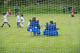 Looking at children's soccer game through soccer goal net.
