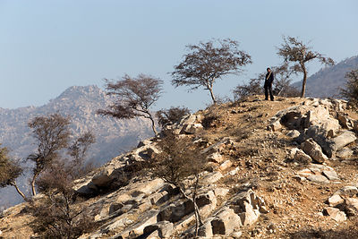 Goat herder on old gneiss rocks outside, Narwar village, Rajasthan, India