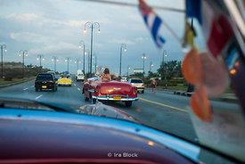 Tourists riding antique cars through Havana, Cuba.