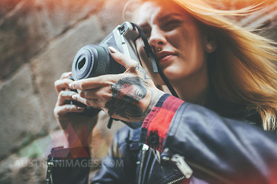 Tattooed woman's hands holding  reflex camera