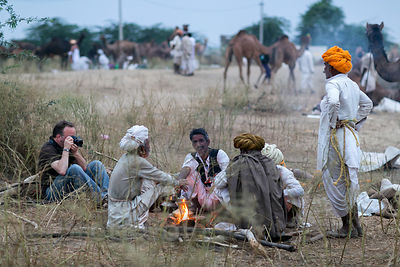 A veteran photojournalist (left) shows the right way to photograph in India, sitting on the ground, interacting with the people, being respectful and open and friendly, Pushkar, Rajasthan, India