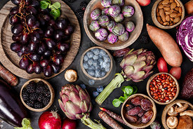 Assortment raw organic of purple ingredients: eggplants, artichokes, potatoes, onions, berries, nuts, carrots, brussel sprouts, grapes over dark background. Top view with space. Food frame