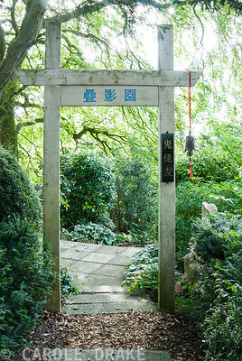 "Chinese gateway marking entrance to garden of 10,000 Shadows planted with mostly non-Chinese plants, hence the vertical sign ""Friendship with foreign devils"". Chinese buddha on right. Beggars Knoll, Newtown, Westbury, Wiltshire, UK"