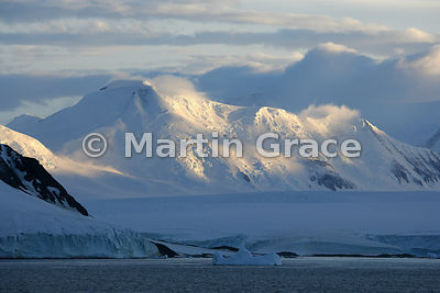 Spectacular sunlight on mountains in Marguerite Bay, West Graham Land, Antarctica, with glacier, cloud and blue sky