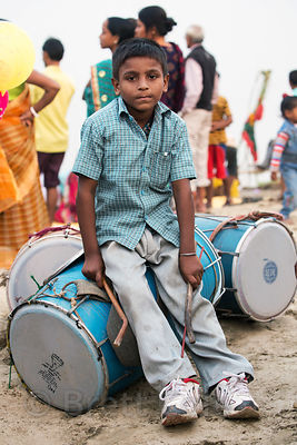 A boy plays drums during Chhath Puja, Varanasi, India. Chhath Puja is a devotion to the Sun God Surya in which people gather at sunset and then on the following sunrise and offer prayers.