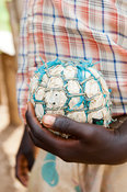 Boy holding home made football, made out of plastic bags and held together with string. Kenya.