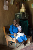 Elderly woman with her baby sitting in a old wooden chair in her house. Kenya